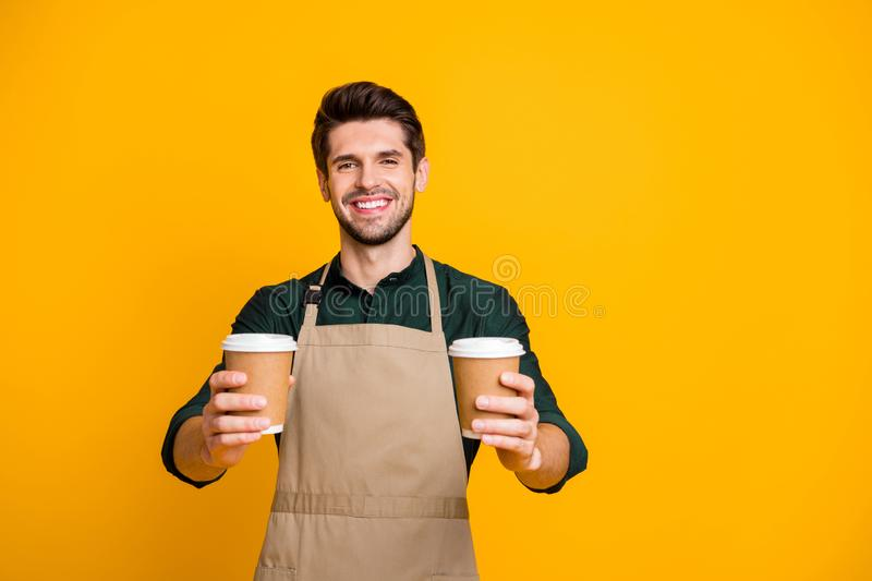Portrait of positive cheerful guy worker in coffee bar shop hold paper card cup offer to his client mug with hot. Portrait of positive cheerful guy worker in stock photos