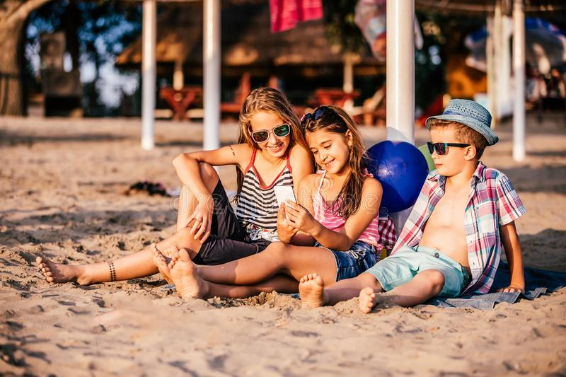Children playing with mobile phones on sandy beach royalty free stock images