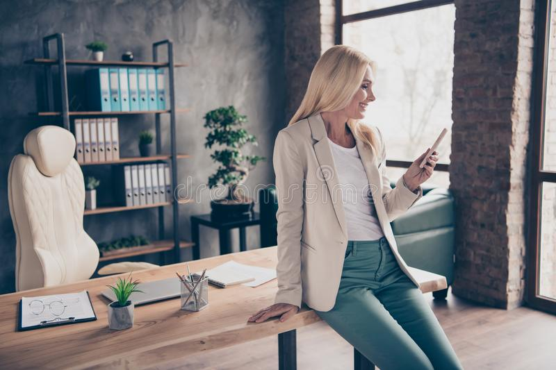 Portrait of positive confident cool blonde hair middle aged businesswoman use her cellphone type messages communicate stock photos