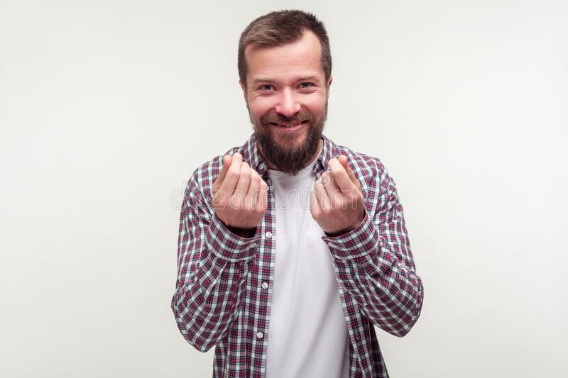 Portrait of positive cunning bearded man showing money gesture and smirking, planning illegal profit.  on white background. Portrait of positive cunning bearded royalty free stock photography