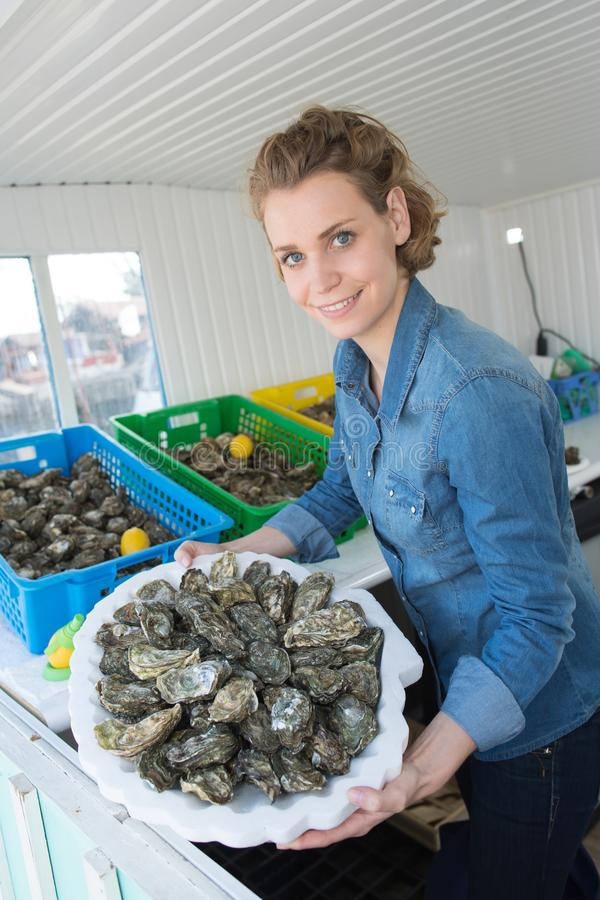 Portrait positive female shop assistant selling fresh oysters royalty free stock photography