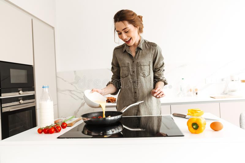 Portrait of positive housewife cooking breakfast or dinner, pour stock image