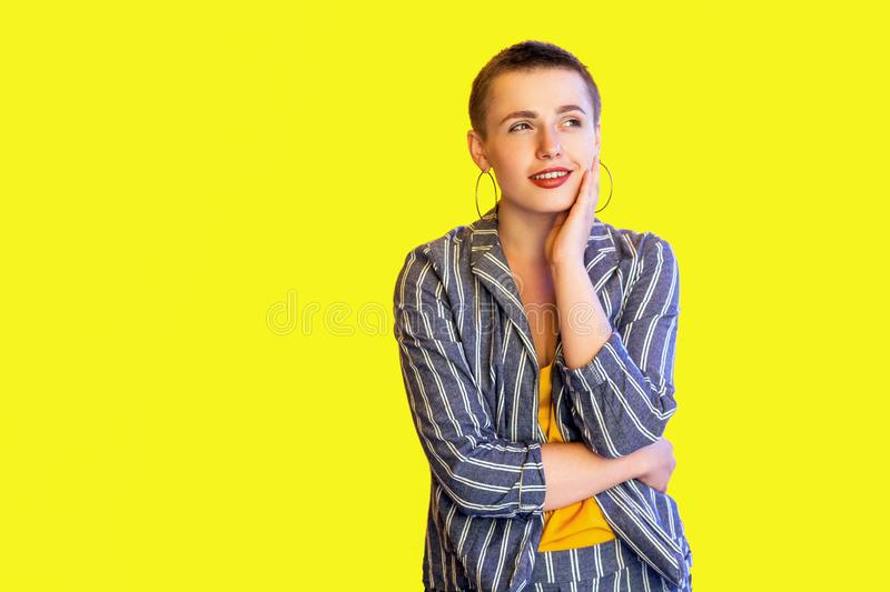 Portrait of positive minded young short hair beautiful woman in casual striped suit standing touching face, looking away and stock photography