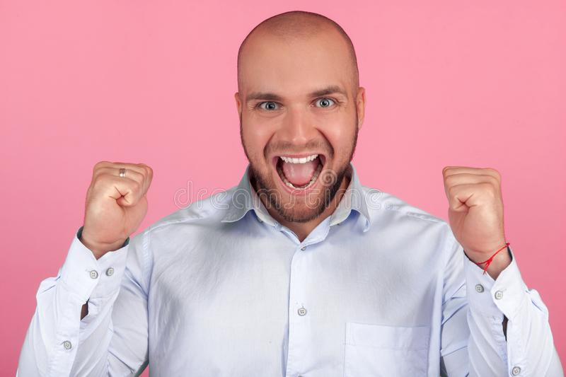 Portrait of positive optimistic bald male celebrates his success, clenches fists, screams with happiness, stands indoor against royalty free stock photos
