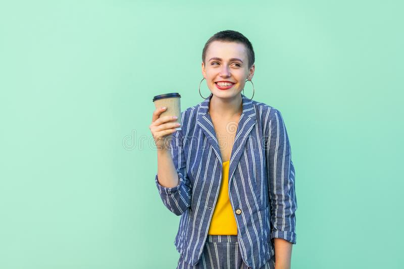 Portrait of positive resting beautiful with short hair young woman in striped suit standing, drinking coffee with toothy smile, royalty free stock photos