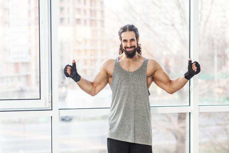 Portrait of positive satisfied sporty young adult muscular trainer man with curly long hair standing with raised heavy arms, royalty free stock photo