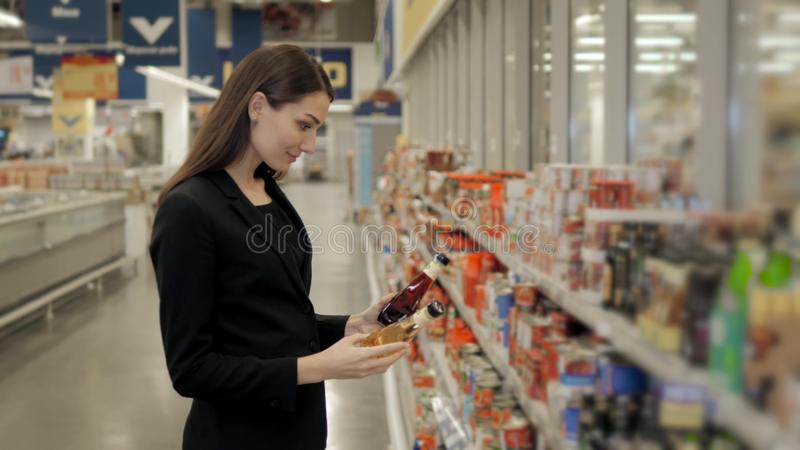 Portrait of positive woman girl buying conserve hot chilli tomato sauce or balsamic vinegar in grocery shop. Portrait of positive woman and cheerful glad girl royalty free stock photography