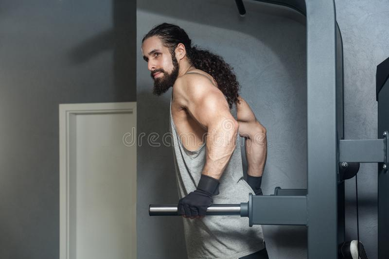 Portrait of powerful confident young adult strong man with long curly hair working out in gym, hanging on horizontal bar with stock photography