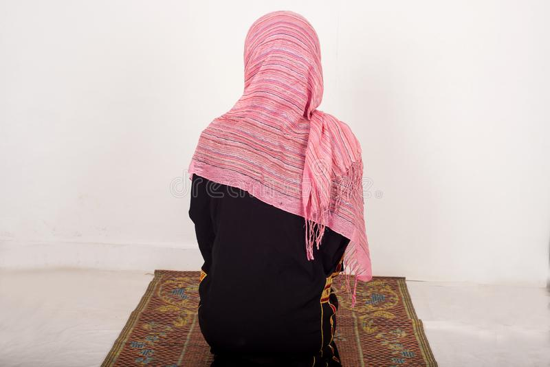 Portrait of praying muslim woman, indoors stock photo