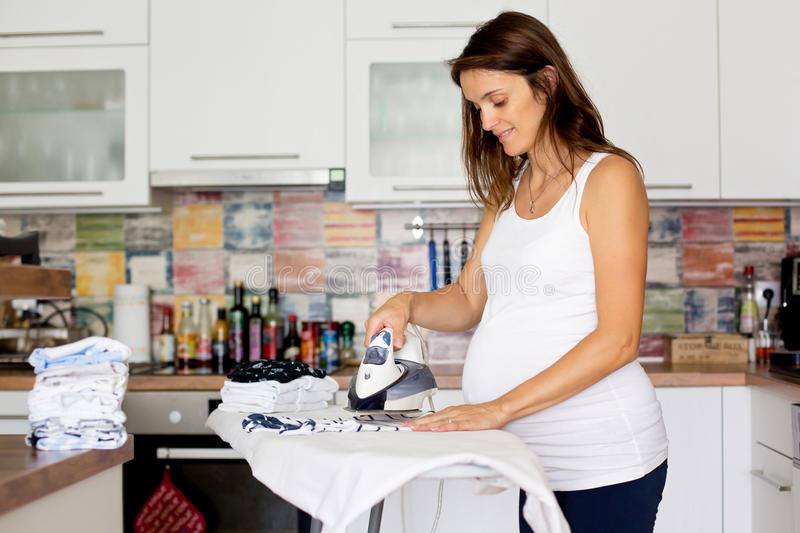 Portrait of pregnant woman ironing her unborn baby`s clothes at royalty free stock photography