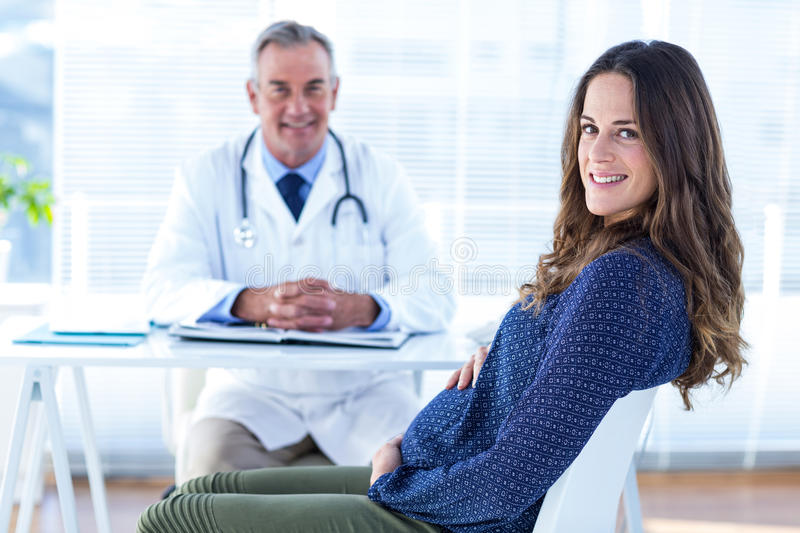 Portrait of pregnant woman with male doctor in clinic. Portrait of smiling pregnant women with male doctor white sitting in clinic royalty free stock photo