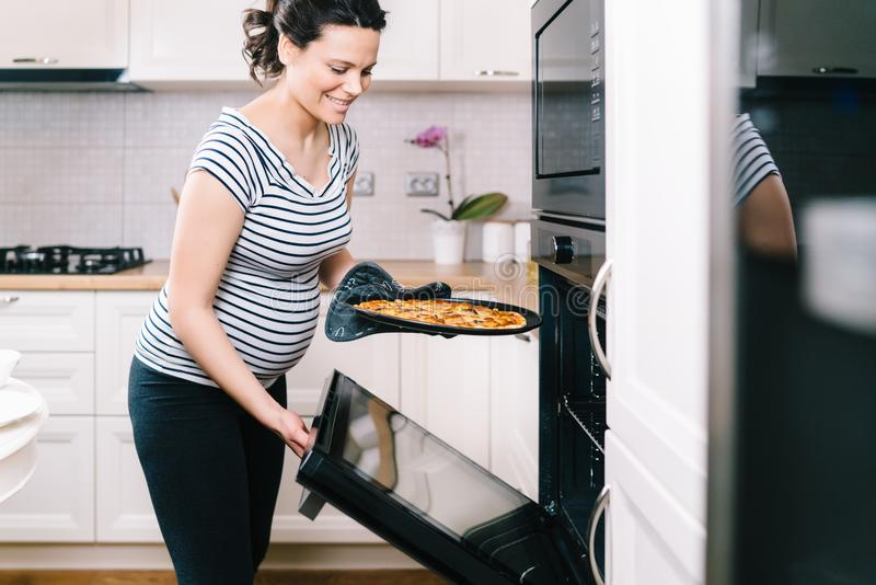 Portrait of pregnant woman preparing pizza at home stock images