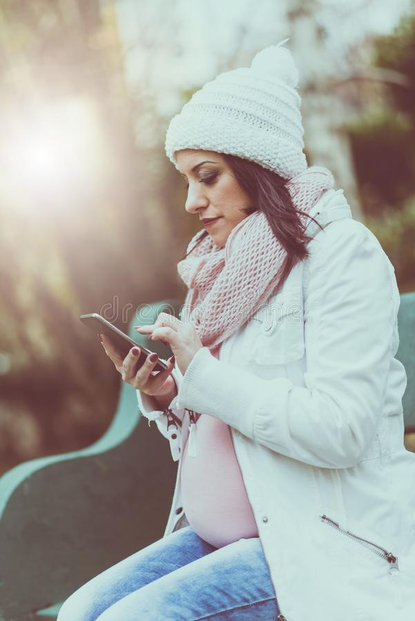 Portrait of pregnant young woman sitting on a bench and using her mobil phone, light effect royalty free stock images