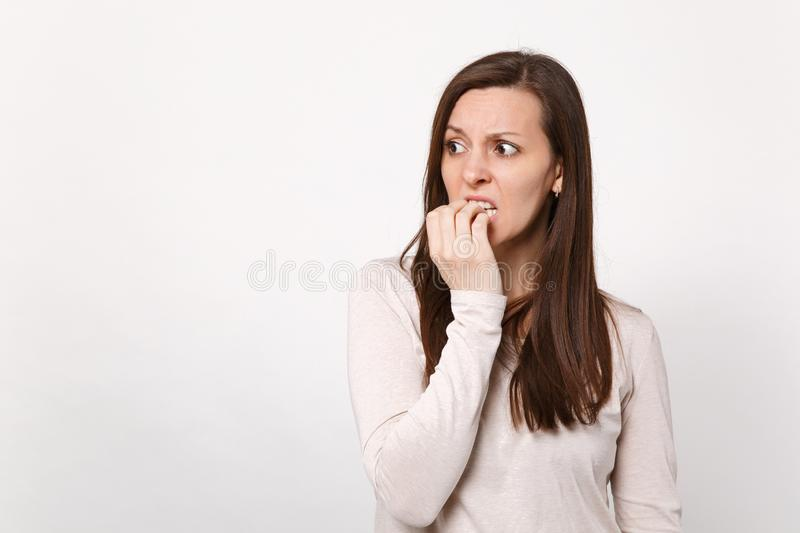 Portrait of preoccupied shocked young woman in light clothes looking aside, gnawing nails isolated on white wall. Background in studio. People sincere emotions stock photography