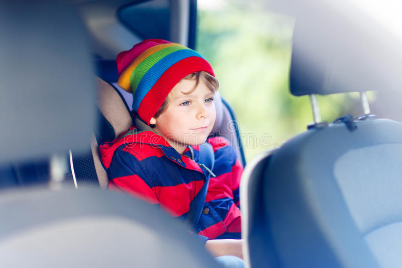 Portrait of preschool kid boy sitting in car. Adorable cute preschool kid boy sitting in car. Child in safety car seat with belt. Safe travel with kids and royalty free stock photos