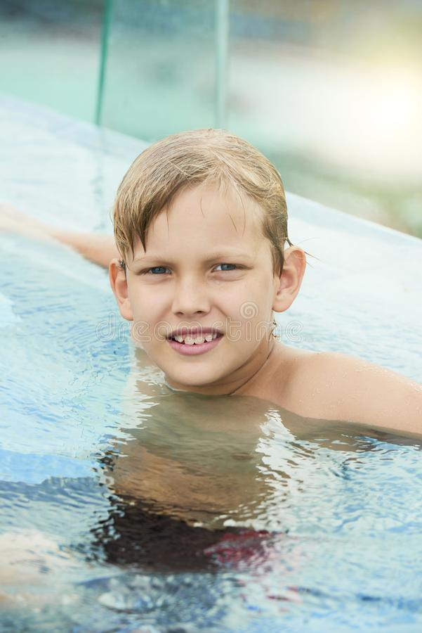 Boy relaxing in swimming pool royalty free stock photo