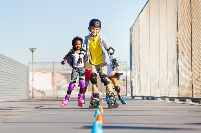 Happy inline skaters rolling at skate park. Portrait of preteen boys and girls, happy inline skaters, rolling at skate park in summer stock image