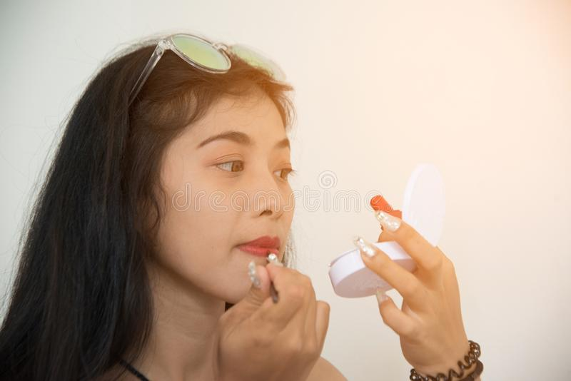 Portrait of pretty Asian woman applies red lipstick . Hand of make-up master, painting lips of young beauty model female. royalty free stock photography