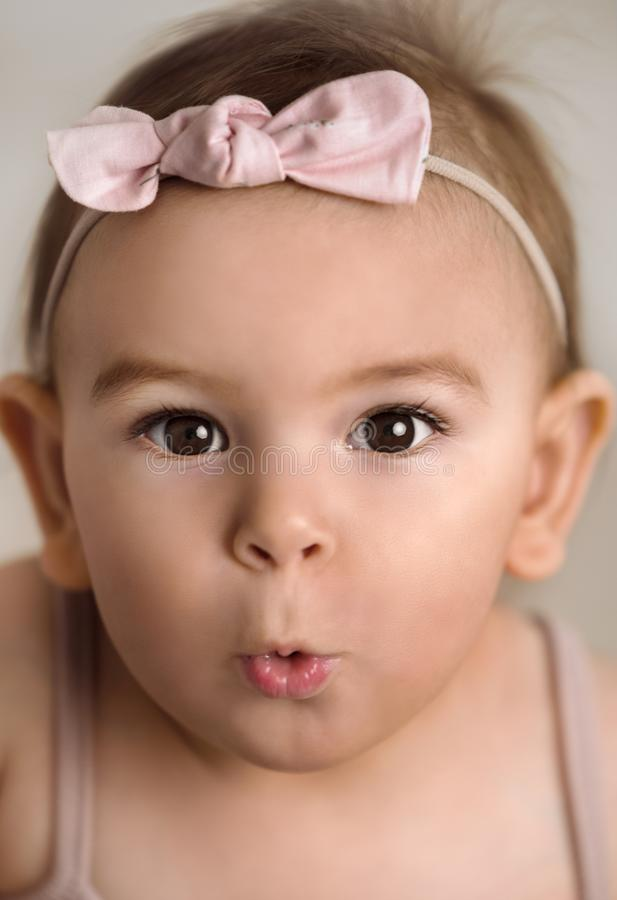 Portrait of a pretty baby girl with white bow on her head close-up stock image