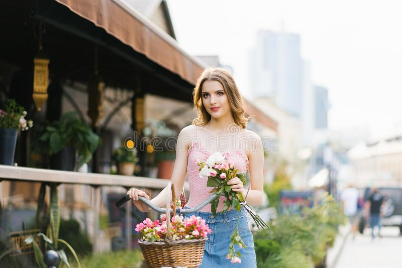 Portrait of a pretty and beautiful girl on the street of the city, bathed in the setting sun. The girl is holding a bouquet of ros stock photos