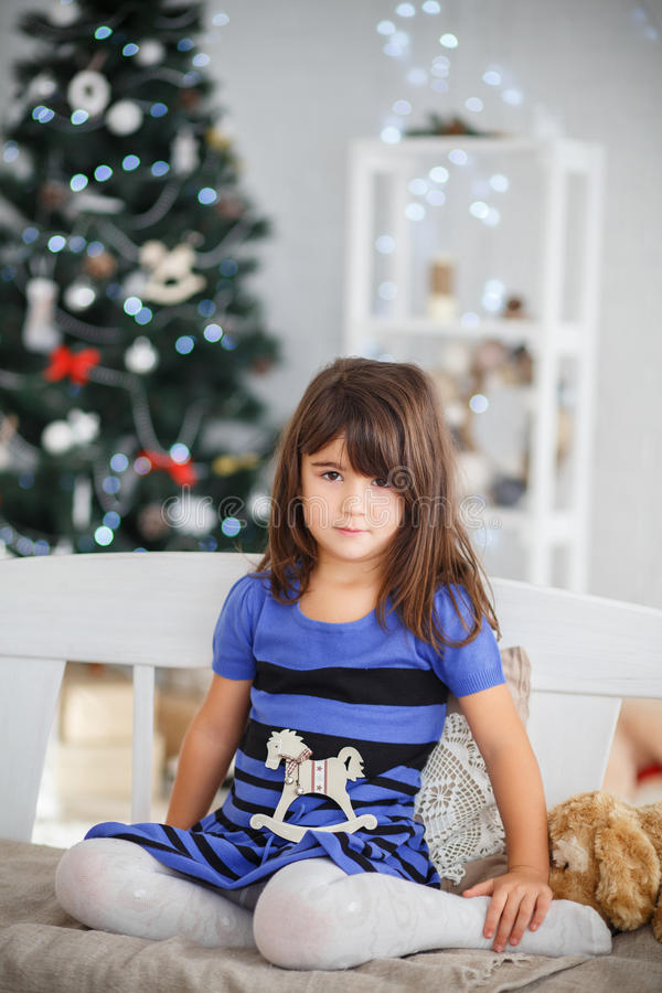 Portrait of pretty brown-eyed little girl in a blue striped dres. S sitting on a white bench in New Year's interior stock photography