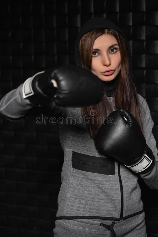 Portrait of pretty brunette. Posing in boxing gloves and gray suit stock photography
