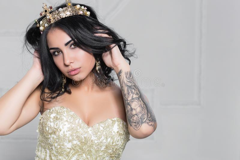 Portrait of a pretty brunette with a tattoo on her arm posing in the studio dressed in an evening dress royalty free stock photos