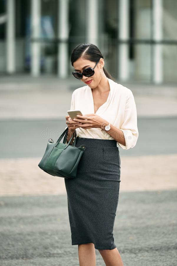 Business woman. Portrait of pretty business lady with smartphone standing outdoors stock image