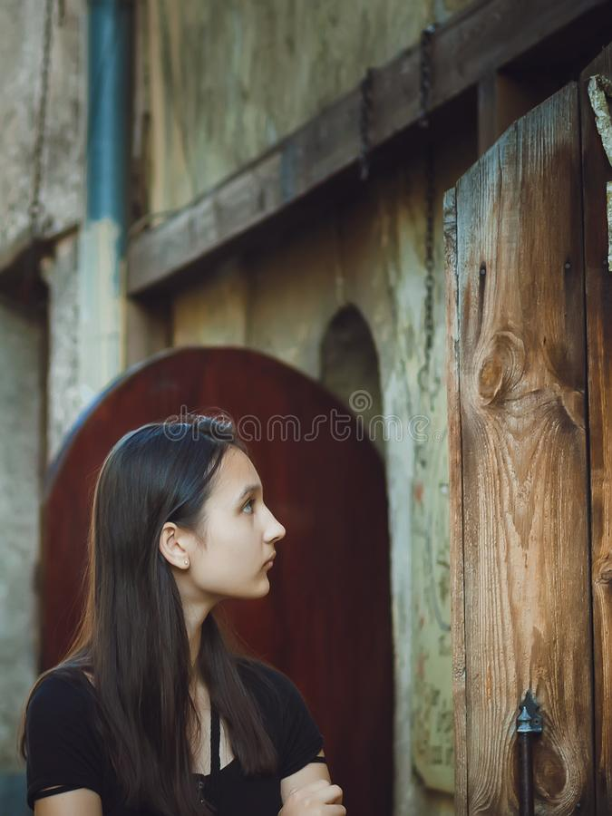 Portrait of a pretty dark-haired girl on the background of an old building stock photography