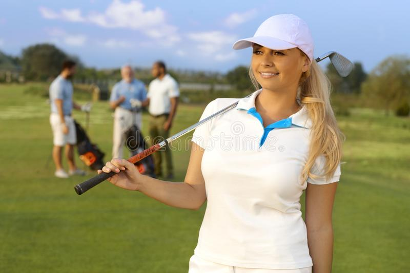 Portrait of pretty female golfer. Portrait of pretty blonde female golfer with golf club, smiling, looking away royalty free stock photography