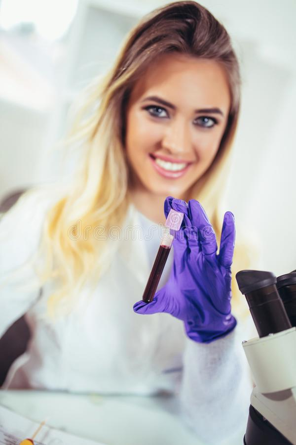 Portrait of pretty female laboratory assistant analyzing a blood sample royalty free stock photos