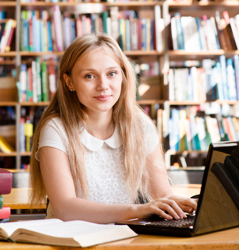 Portrait of a pretty female student with laptop in library stock photos