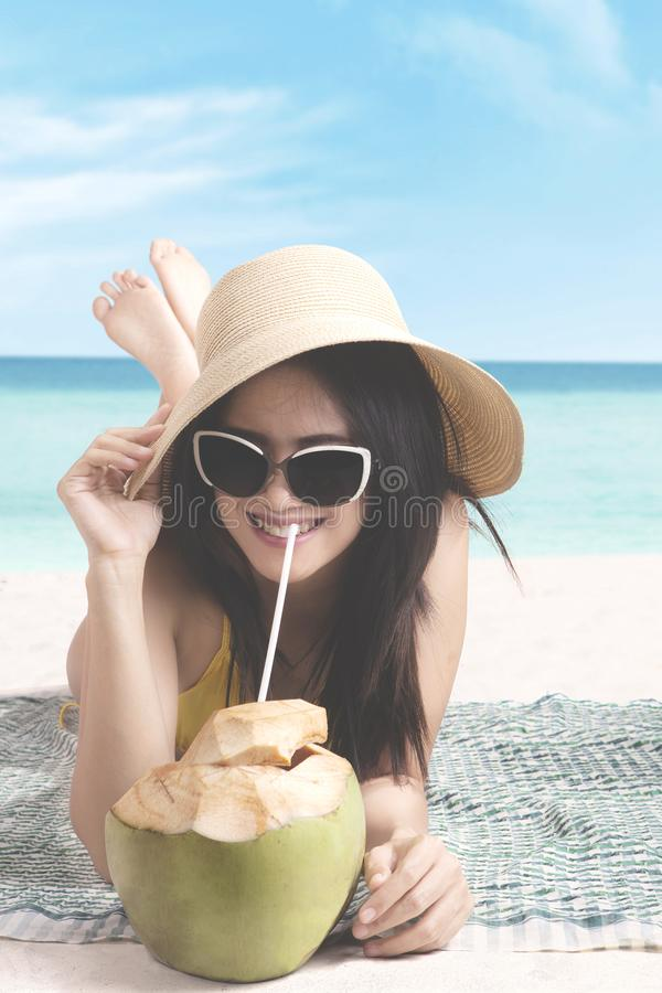 Female drinking coconut water on the beach stock photo