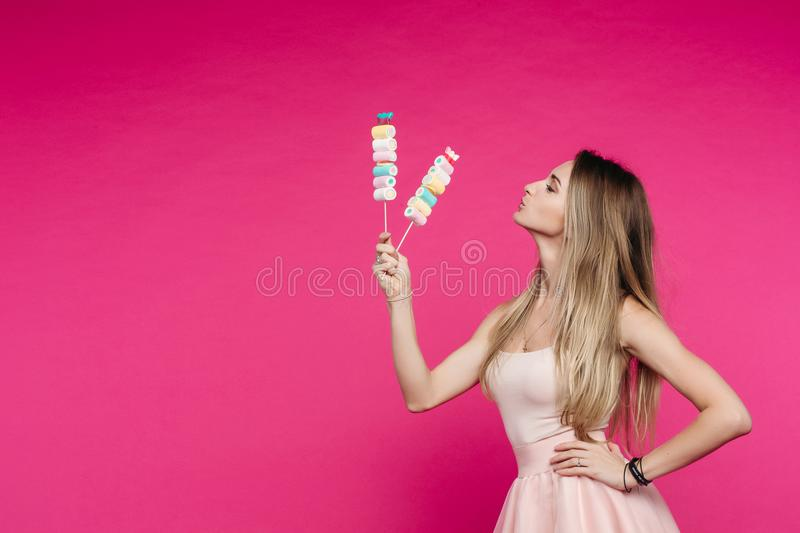 Funny girl like doll with marshmallow candy on stick. stock photo