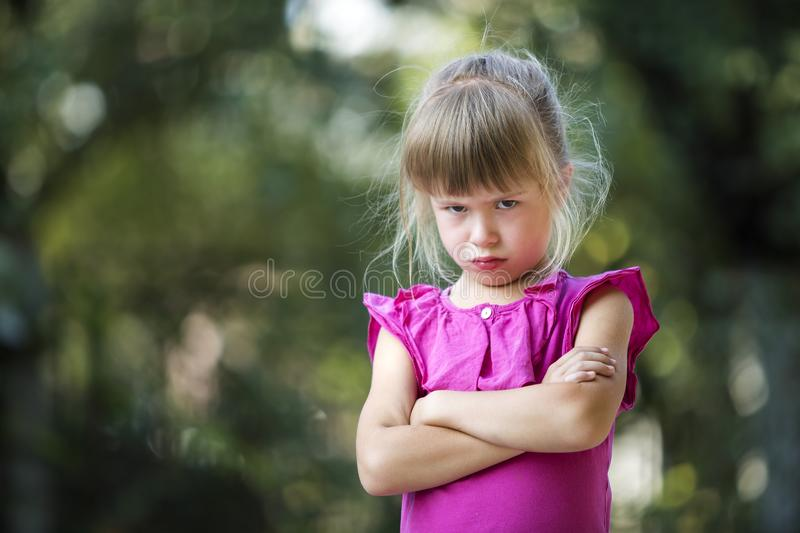Portrait of pretty funny moody young blond child girl in pink sleeveless dress looks in camera feeling angry and unsatisfied on b. Lurred summer green copy space stock photo