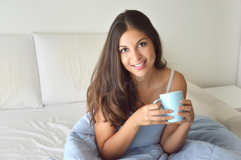 Portrait pretty girl drinking coffee or tea on bed in the morning in apartment with copy space royalty free stock images