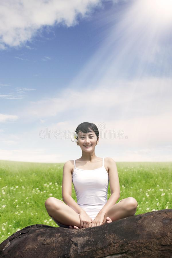 Happy girl practicing yoga in the flower field. Portrait of pretty girl looks happy after practicing yoga in the flower field royalty free stock photos