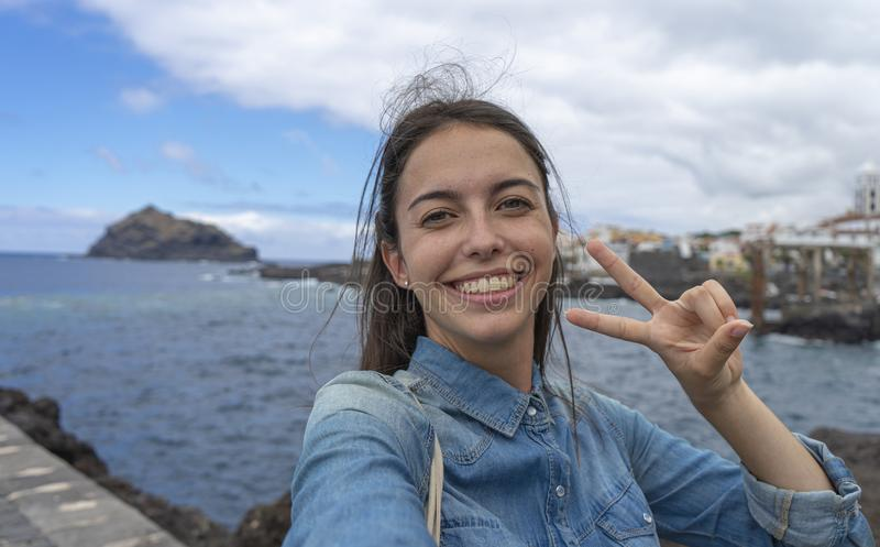Portrait of pretty girl on port in sea town with victory sign making selfie with cellphone showing teeth to the camera. Young royalty free stock photo