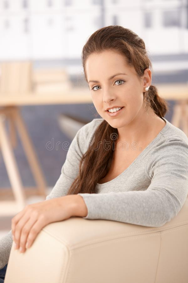 Portrait of pretty girl sitting on sofa smiling. Portrait of pretty girl sitting on sofa at home, smiling stock photography