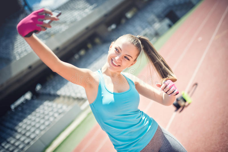 Portrait of pretty girl smiling and taking a selfie while training. Beautiful woman taking pictures of herself. Social media, te stock photos