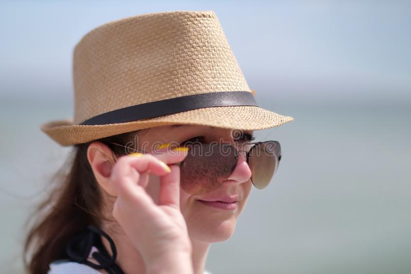 Portrait of pretty girl in sunglasses and a hat, holding glasses with hand, close-up stock photo