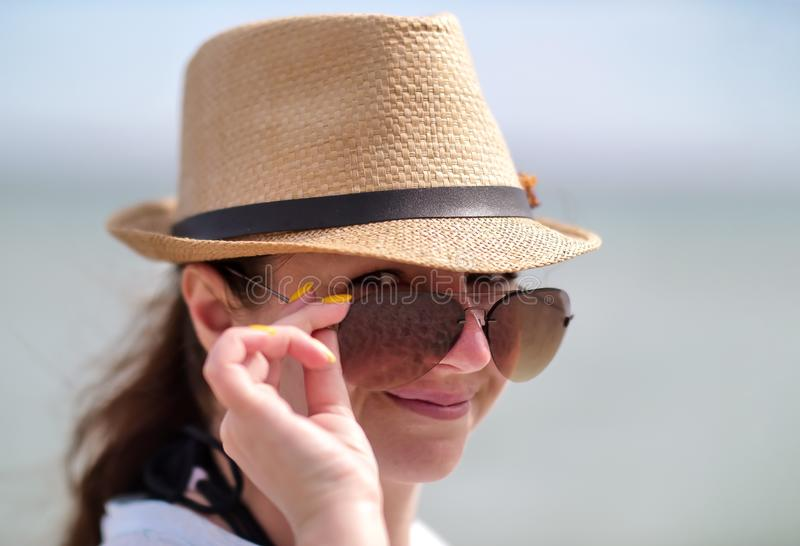 Portrait of pretty girl in sunglasses and hat, holding glasses with hand, looks into camera, close-up royalty free stock image