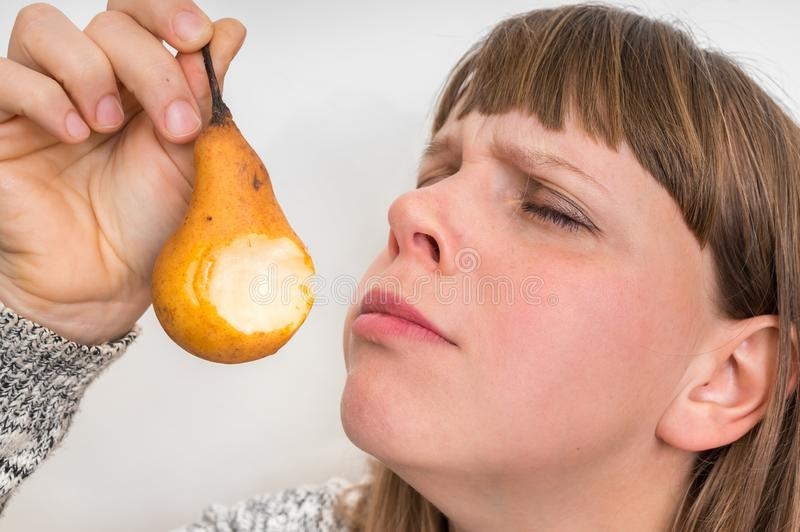 Portrait of pretty girl with yellow pear. In front her face stock photo