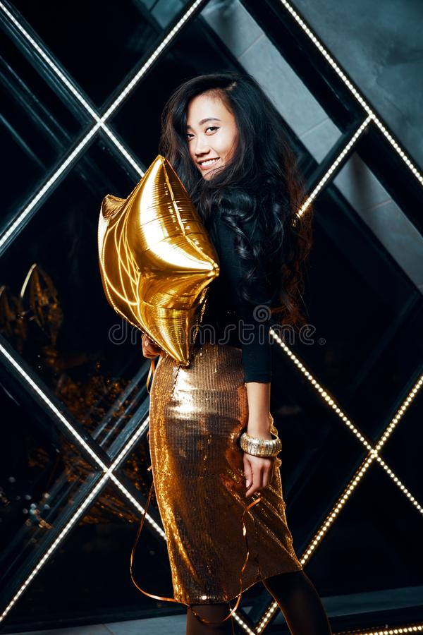Portrait of pretty happy asian woman having fun and holding golden balloon royalty free stock photos