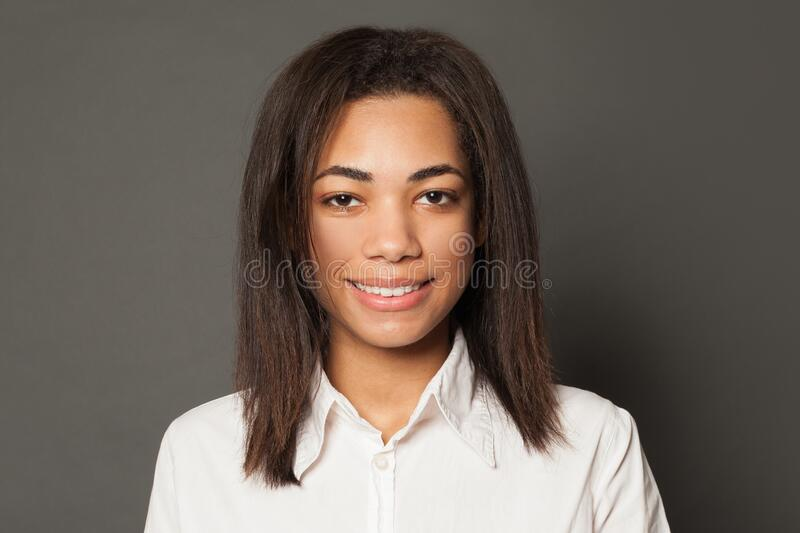 Portrait of pretty happy smart African American woman student on gray background, face close up stock photography