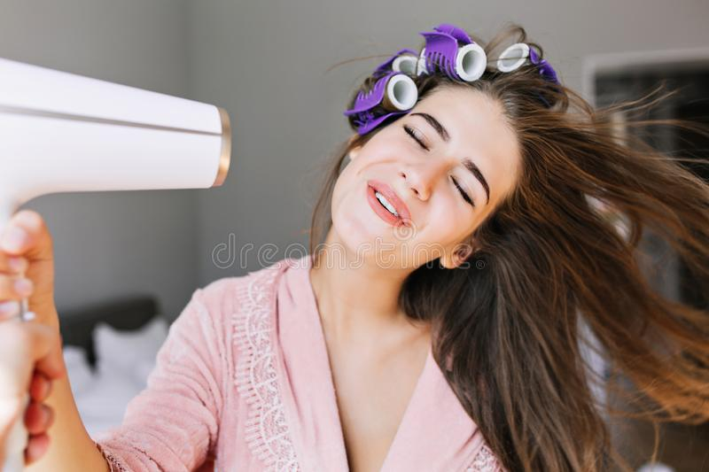 Portrait pretty housewife in pink bathrobe with curler at home. She looks enjoyed at drying hair. Portrait pretty housewife in pink bathrobe with curler at home royalty free stock photography