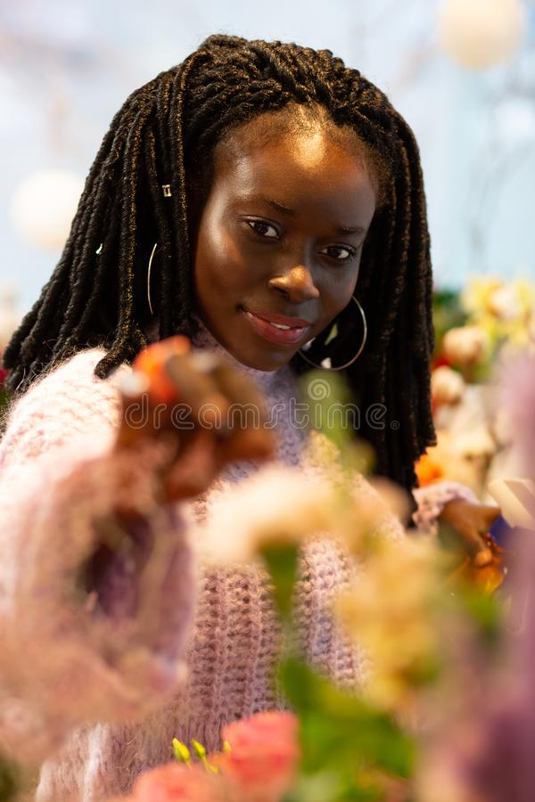 Portrait of pretty international girl that posing on camera. Professional hobby. Delighted female expressing positivity while touching flowers royalty free stock photos