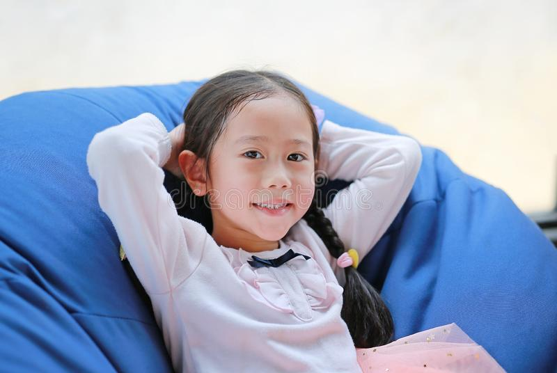 Portrait of pretty little Asian child girl smile and relaxing on fabric sofa with looking camera royalty free stock images