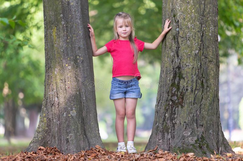 Portrait of a pretty little child girl standing near big tree trunk in summer park outdoors stock photography