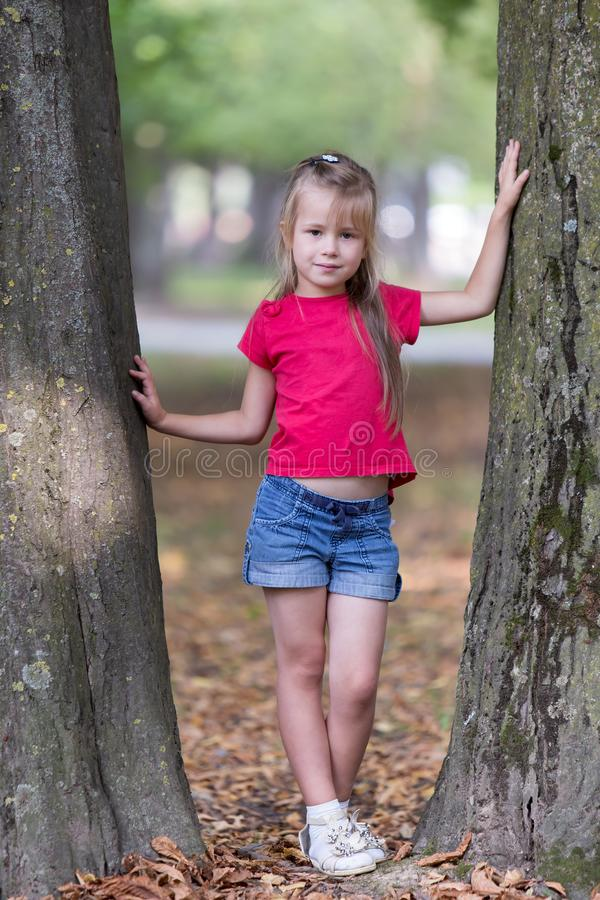 Portrait of a pretty little child girl standing near big tree trunk in summer park outdoors royalty free stock photo